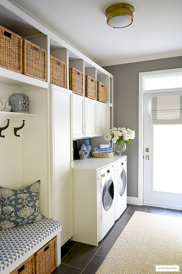 Mudroom + Laundry room with a fresh coastal feel - brass nautical flush mount lighting, natural woven baskets and rug, and plenty of blue and white accents create a fresh and crisp space.