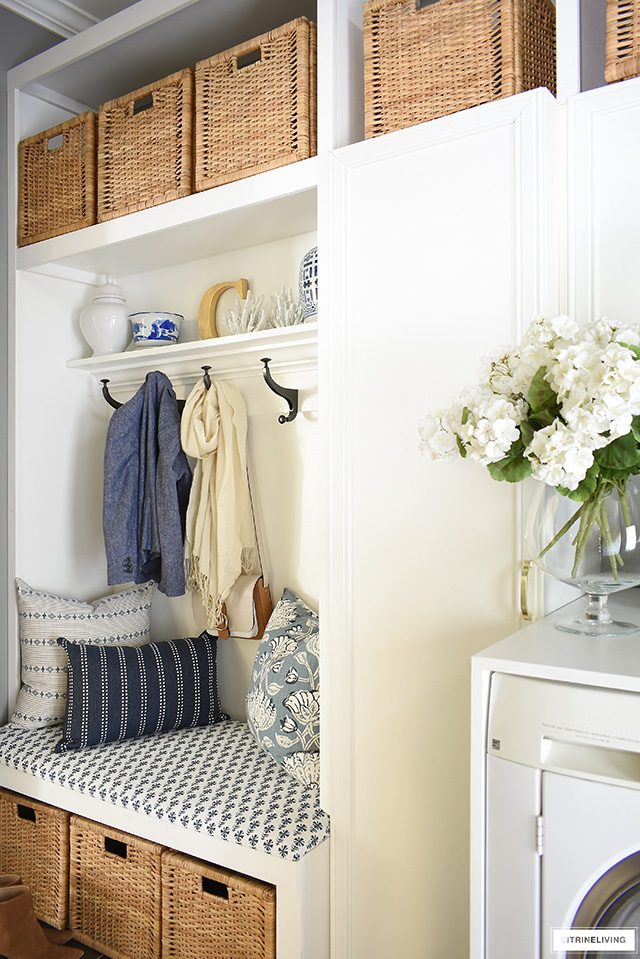 Gorgeous mudroom + laundry room with upholstered bench and shelf and coat hooks.
