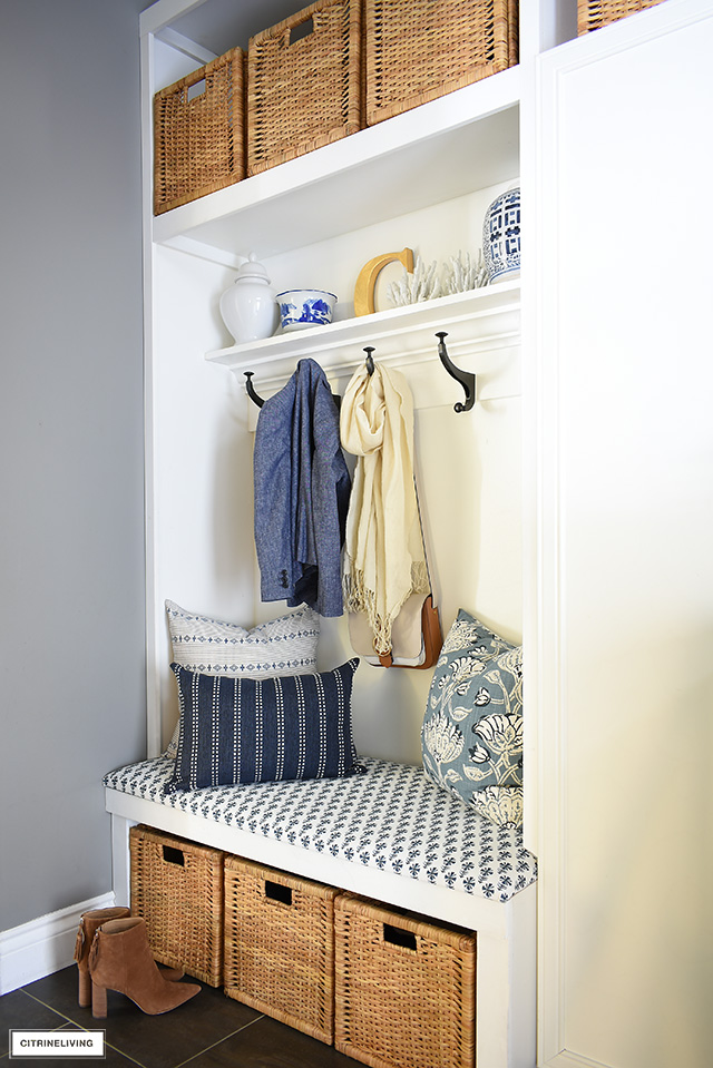 Practical and beautiful, a builtin bench with a mix of blue and white fabrics is gorgeous in a coastal mudroom and laundry room.