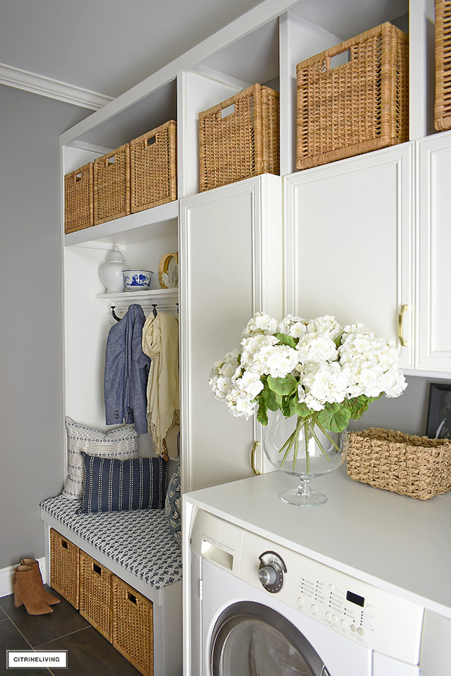 Mudroom/laundry room with builtin upholstered bench, cabinets and baskets for storing seasonal and miscellaneous household items.