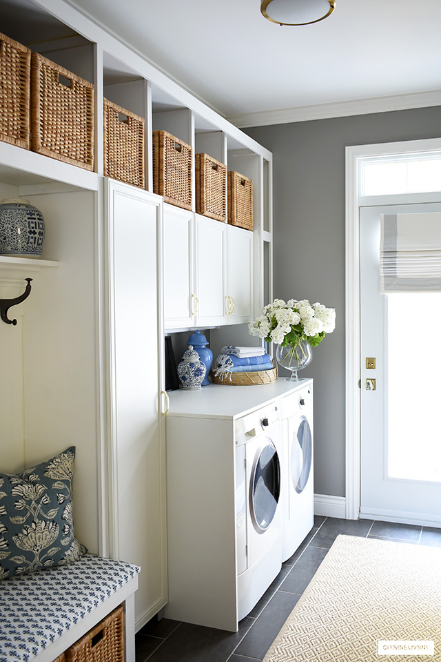 Coastal mudroom and laundry room with builtin cabinets, natural woven Ikea baskets, builtin bench and a beautiful roman shade.
