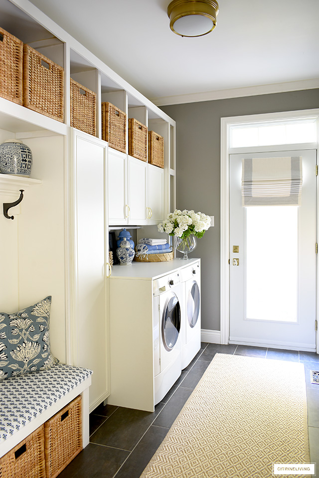 Coastal feel mudroom + laundry room with woven baskets and builtin cupboards for much needed storage, blue and white decor accents and fabric prints are fresh and crisp.