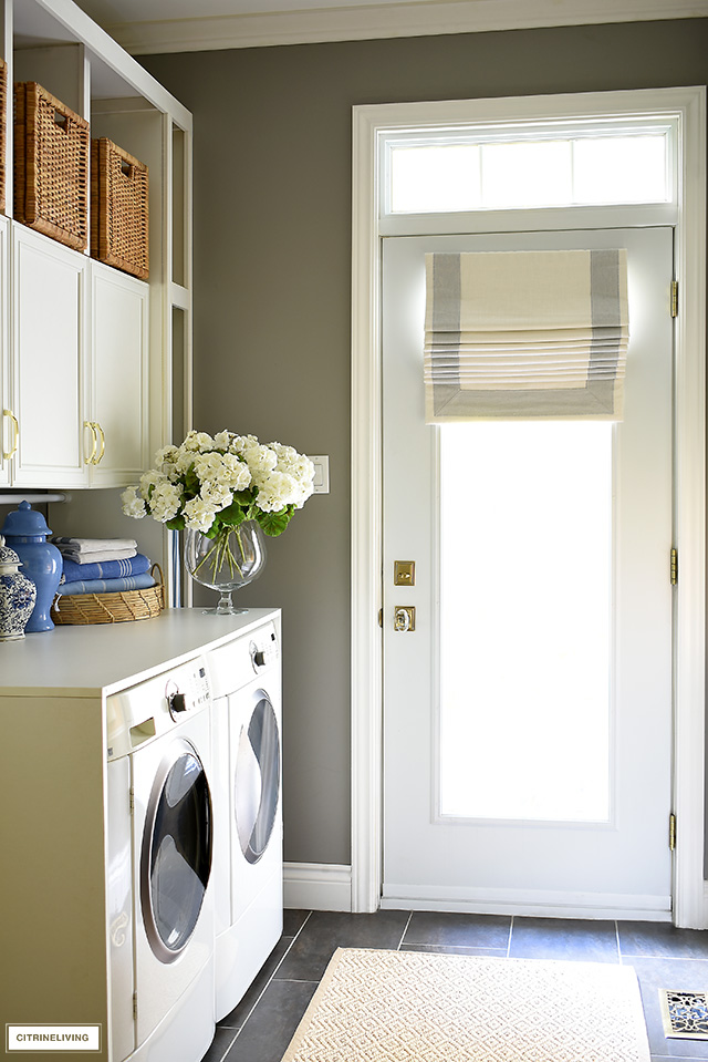 Gorgeous mudroom + laundry room with builtin cabinets, woven baskets and a beautiful custom roman shade.