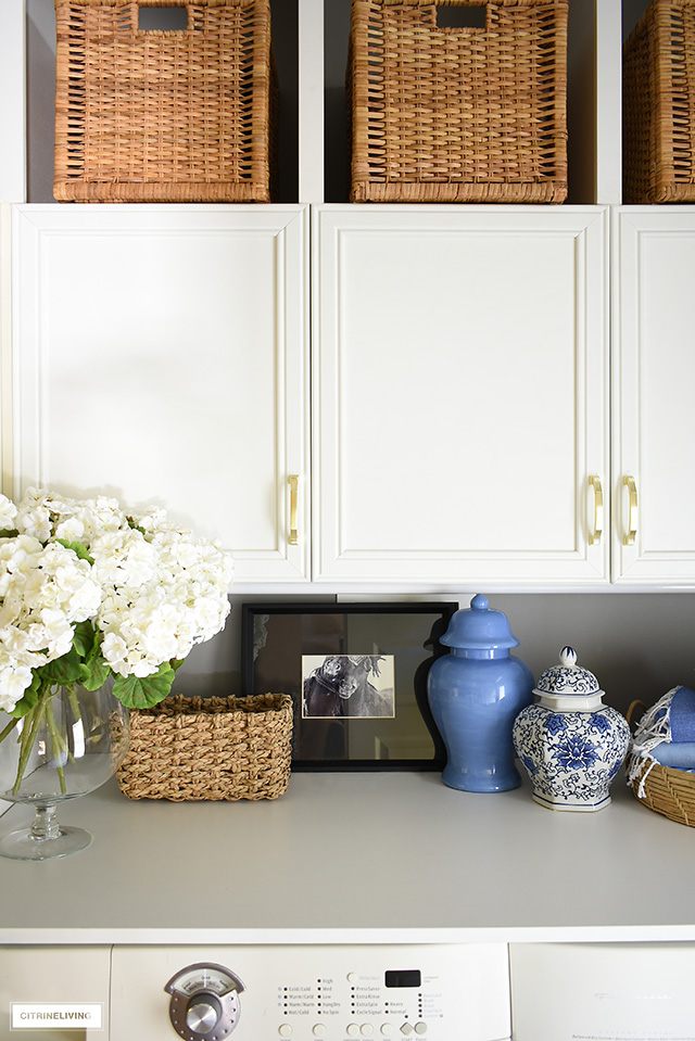 Style your laundry room with pretty details! Beautiful woven baskets and trays, faux blooms, framed art and ginger jars are a chic touch.