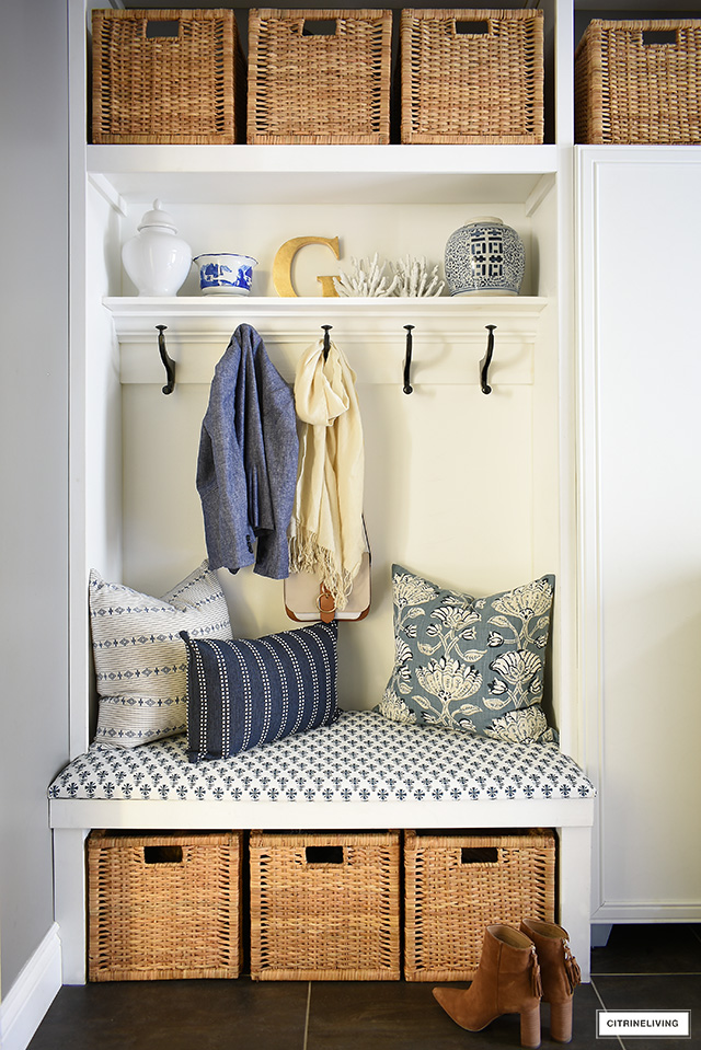 A beautiful builtin upholstered bench with blue and white block print fabric and pillows is a fresh and crisp element in a coastal themed laundry room.