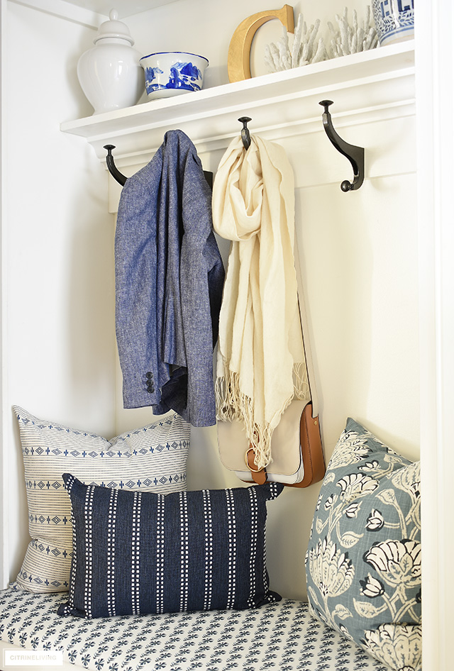 Beautiful blue and white pillows and bench fabric are a gorgeous addition to this coastal look mudroom + laundry room builtin bench.