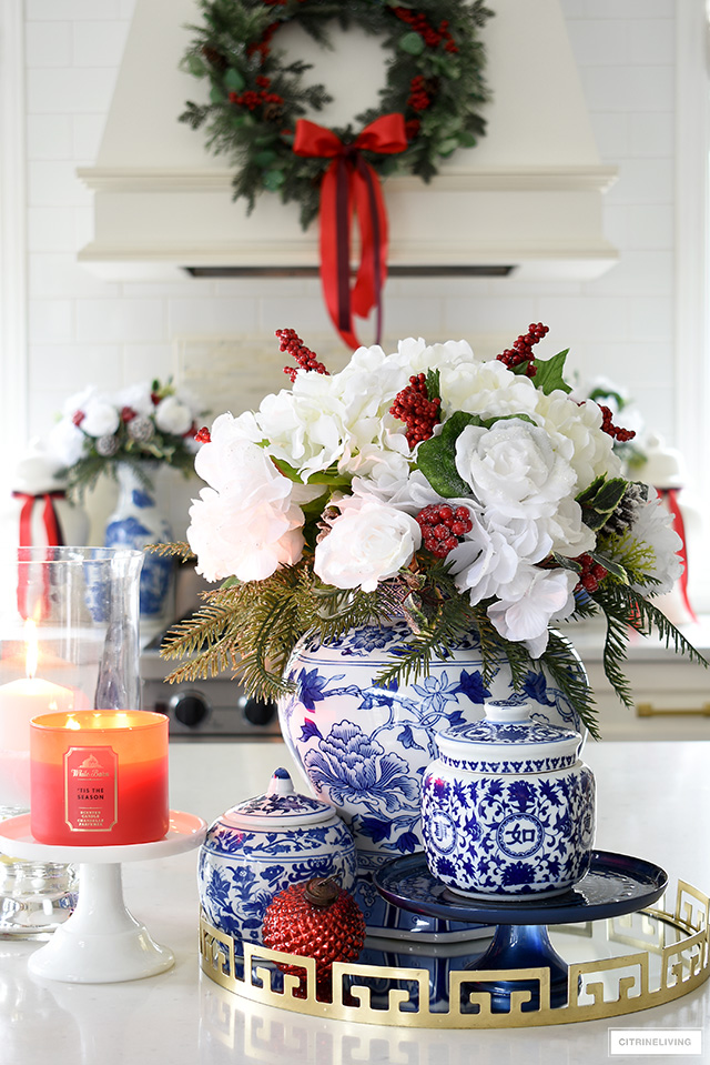 Gorgeous Christmas floral arrangement with white hydrangeas, peonies, roses, red verses and greenery, is beautiful against a blue and white ginger jar.