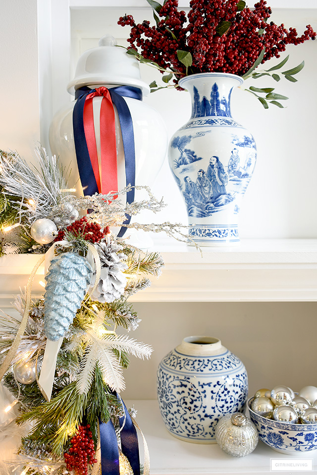 Christmas garland closeup - red berries, greenery and ribbons add special touches! Arrange blue and white vases and jars with simple ornaments for a beautiful display.