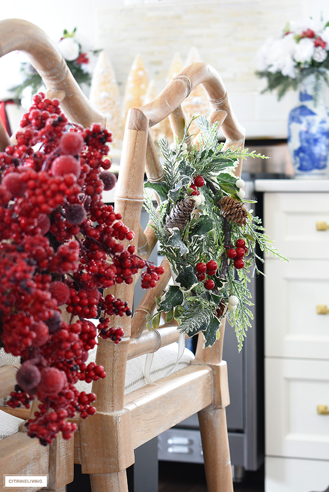 Dress up your kitchen barstools with a mix of different Christmas wreaths in greens and red frosted berries to add visual interest!