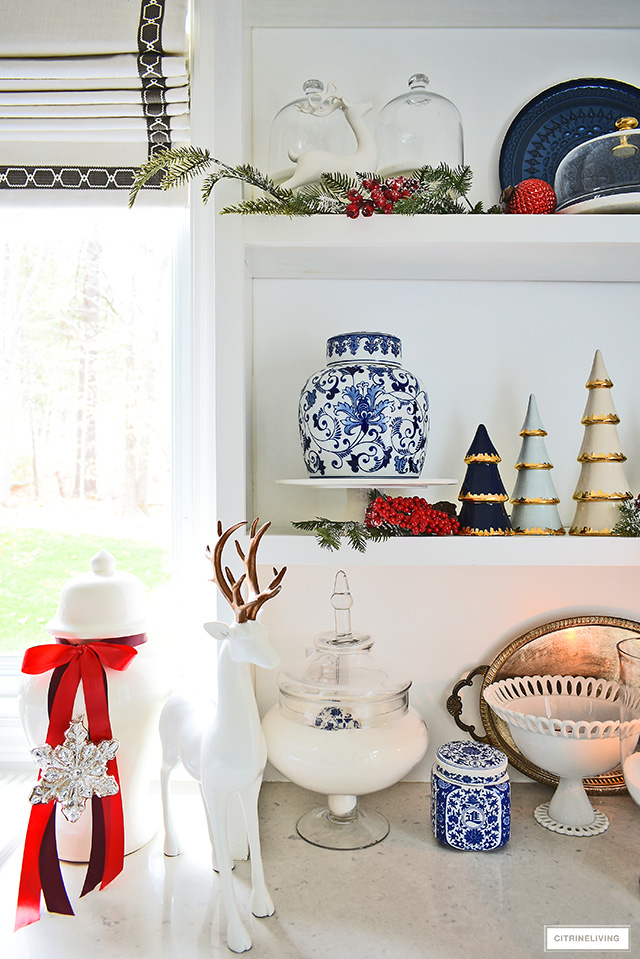 Kitchen shelves styled with blue and white ginger jars, ceramic Christmas trees, and pine branches with red berries - a beautiful and classic look!