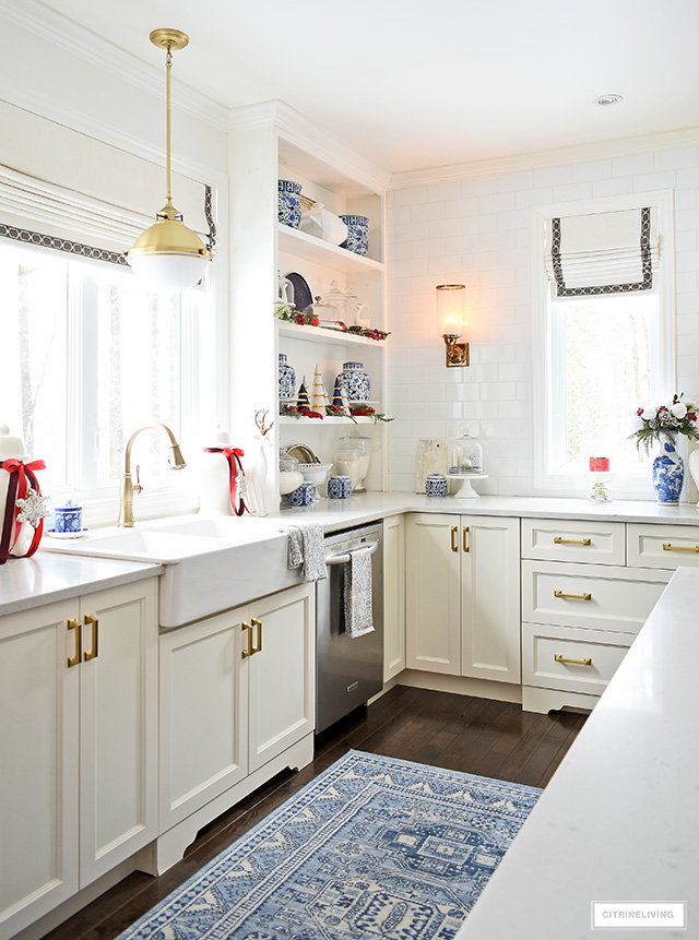 White kitchen decorated for Christmas with blue and white ginger jars and vases, red accents and greenery is traditional and sophisticated.