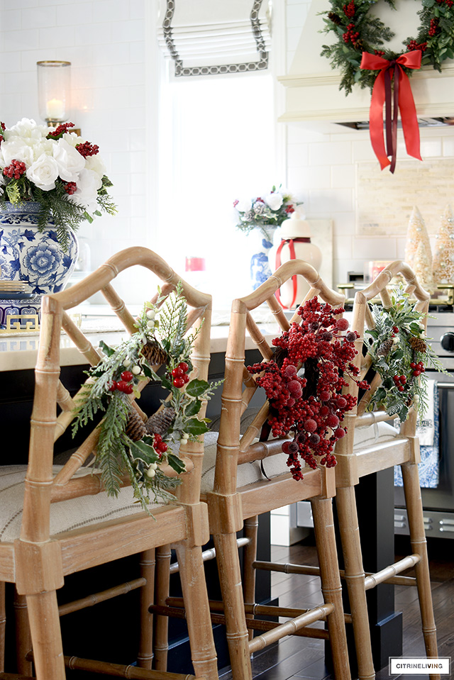 Christmas kitchen decor with festive wreaths tied onto barstools.