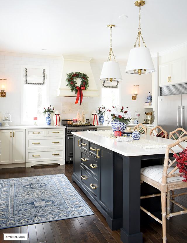 Christmas kitchen decorating with blue and white chinoiserie pieces, white floral arrangements, greenery and red berry accents is a sophisticated take on the holiday season.