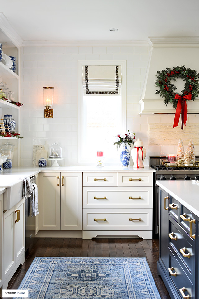 Christmas kitchen decor - style your hood with a pretty wreath dressed up with red berries and ribbon.