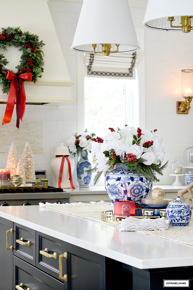 Christmas kitchen decor ideas - blue and white chinoiserie styled with holiday greenery, red berries and beautiful white florals.