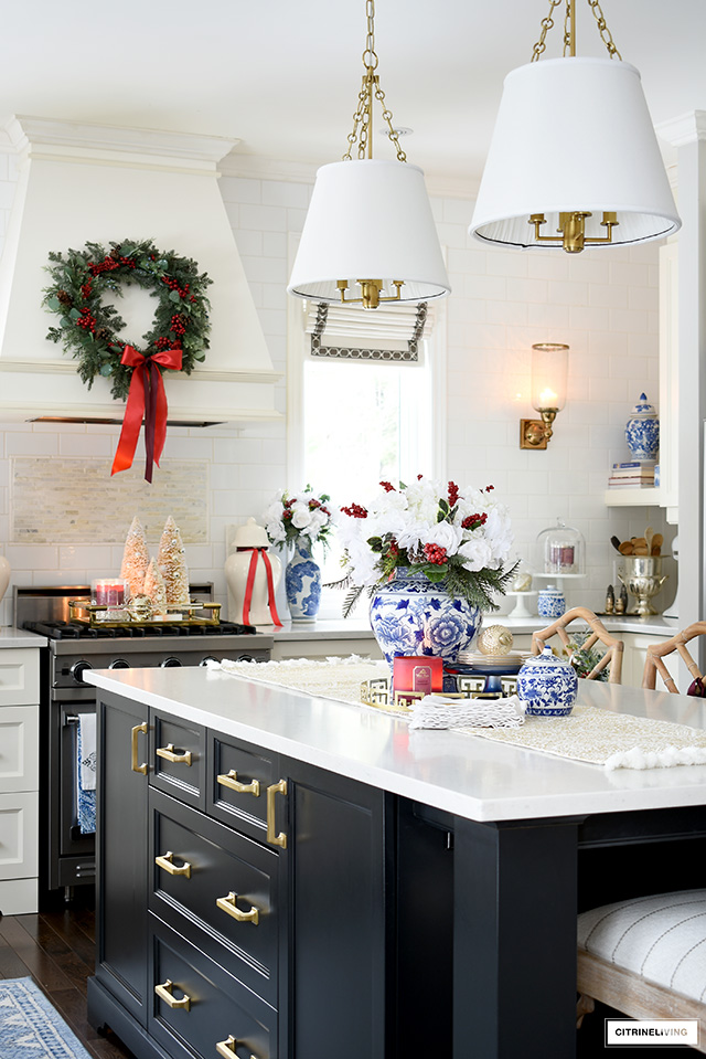 Beautiful Christmas kitchen decor with blue, white, red, and greenery is sophisticated and elegant.