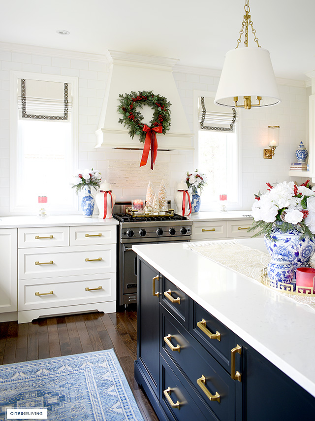 Christmas kitchen decorated with blue and white chinoiserie pieces, white flowers, greenery and red accents.