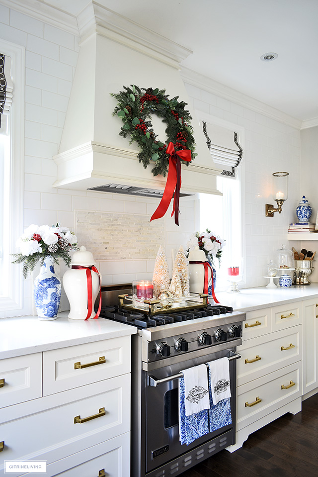 Beautiful Christmas kitchen decorating - range hood styled with a green wreath with red berries, stove flanked with holiday floral arrangements and ginger jars.