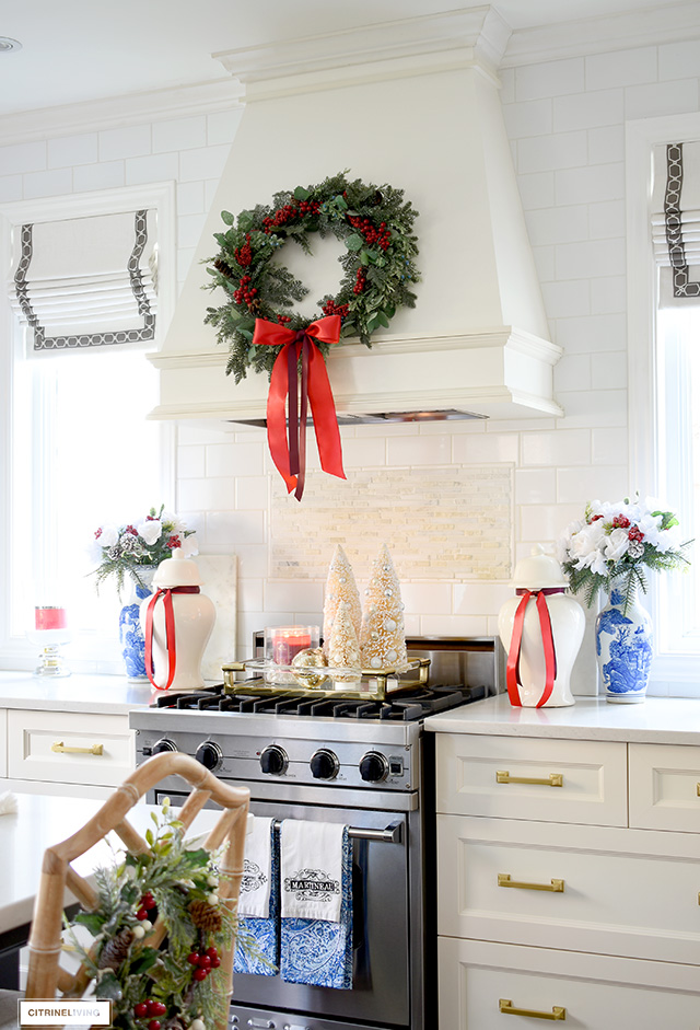 Beautiful Christmas kitchen decorating - green wreath with red berries displayed on the range hood creates a beautiful focal point.