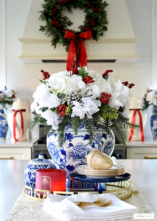 Create a beautiful Christmas kitchen centrepiece with white florals, red berries and holiday greenery in a blue and white ginger jar.