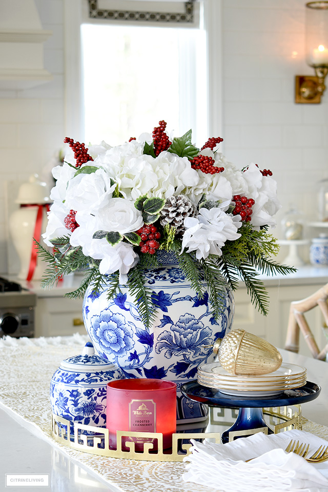 Gorgeous Christmas floral arrangement with white roses, hydrangeas, holiday greenery and red berries.
