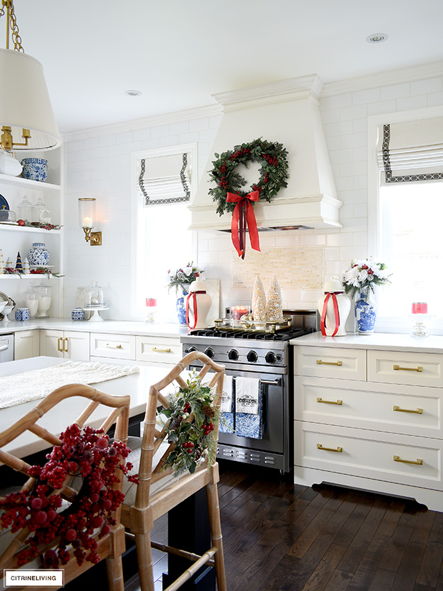 Christmas kitchen with blue, red, white, and holiday greenery.