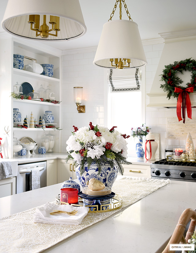 Christmas kitchen decor - island styled with a holiday arrangement, scented candles and pretty dishes.