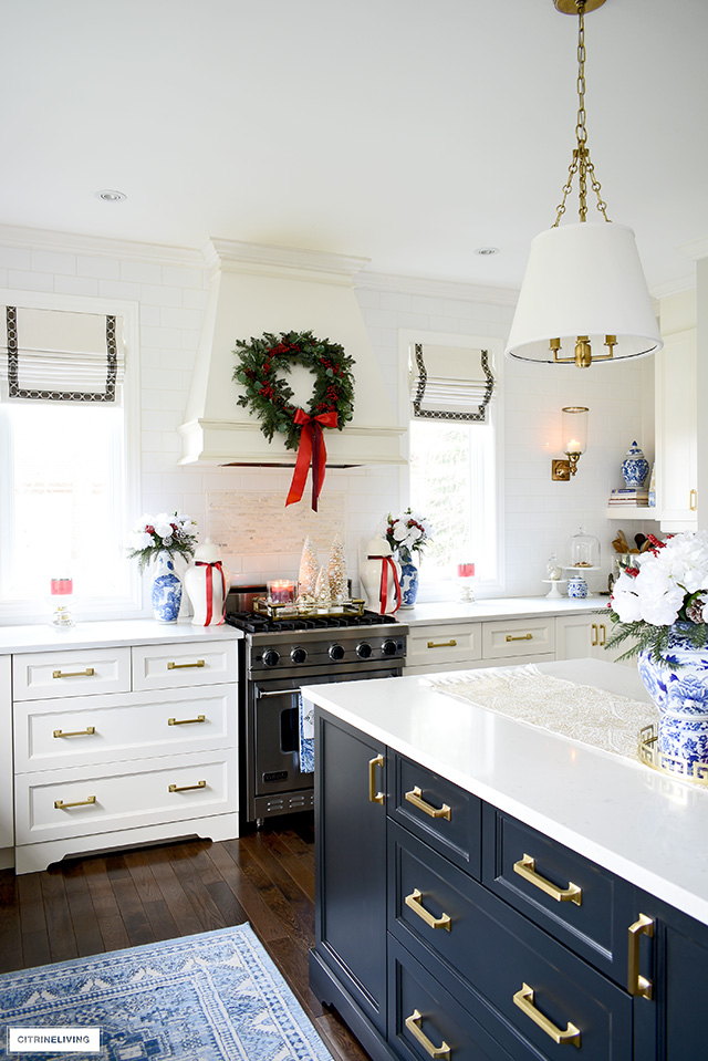 Christmas kitchen decor with blue and white chinoiserie and greenery with red berries.