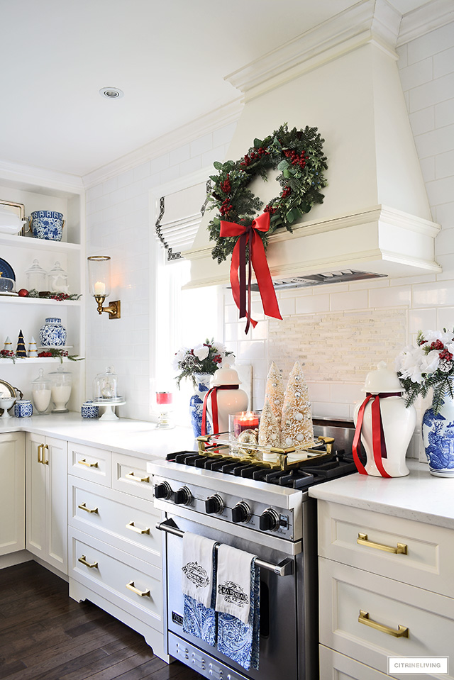 Beautiful Christmas kitchen decorating - range hood styled with a green wreath with red berries