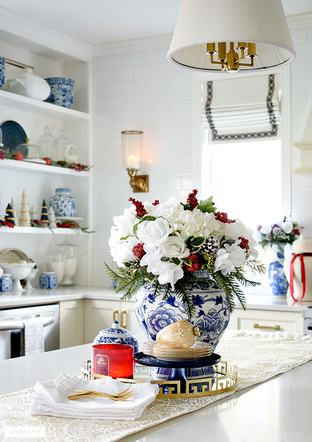 Beautiful Christmas floral arrangement with white roses and hydrangeas, holiday greenery and red berries is festive and elegant.
