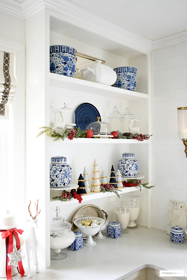 Open kitchen shelves decorated for Christmas with blue and white chinoiserie pieces, apothecary jars, red ornaments, greenery and gold accented Christmas trees in blue and white.