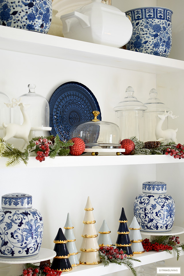 Beautiful kitchen shelves styled for Christmas with blue and white chinoiserie pieces, greenery and red berries and ornaments.