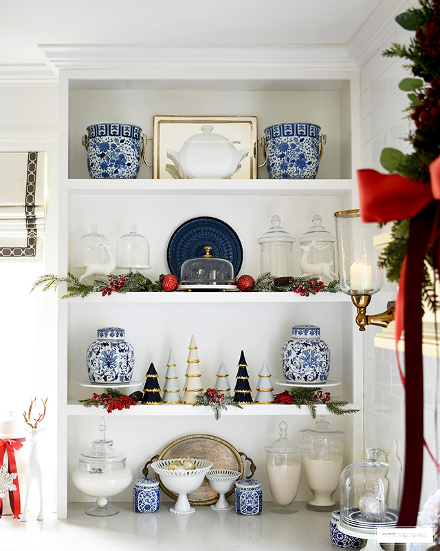Gorgeous kitchen shelves styled for Christmas with blue and white chinoiserie, greenery and red ornaments.