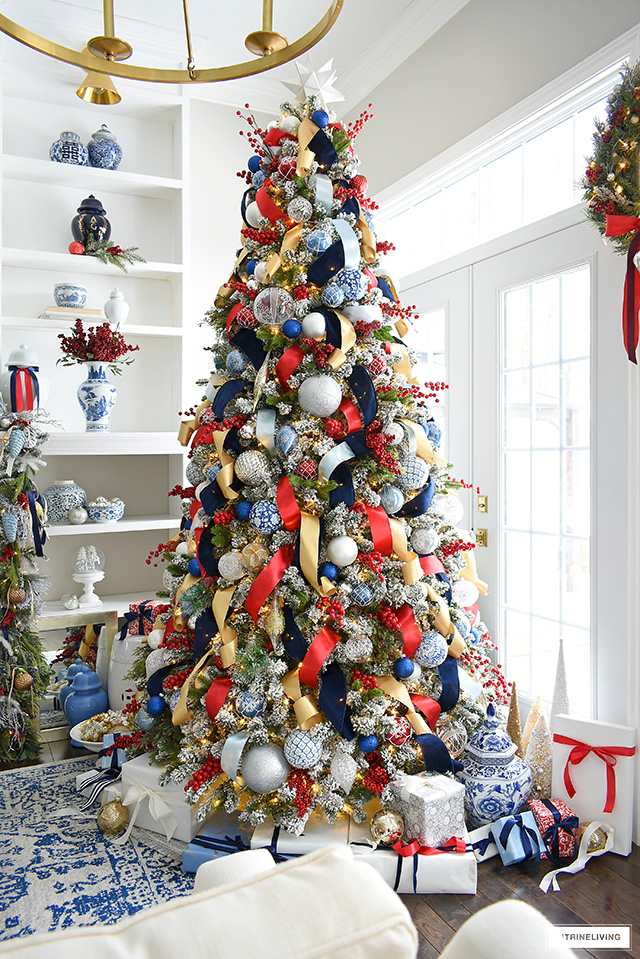 Beautiful flocked Christmas tree with greenery picks, berry picks and red, blue and metallic decorations.