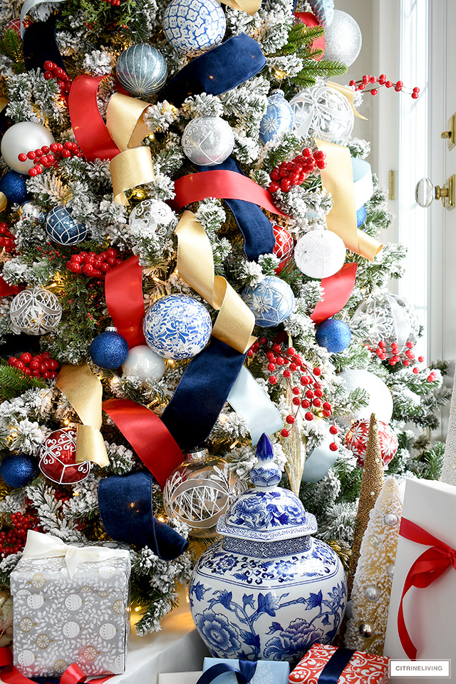 Beautiful flocked Christmas tree with decorations in blue, red, gold, silver and white.