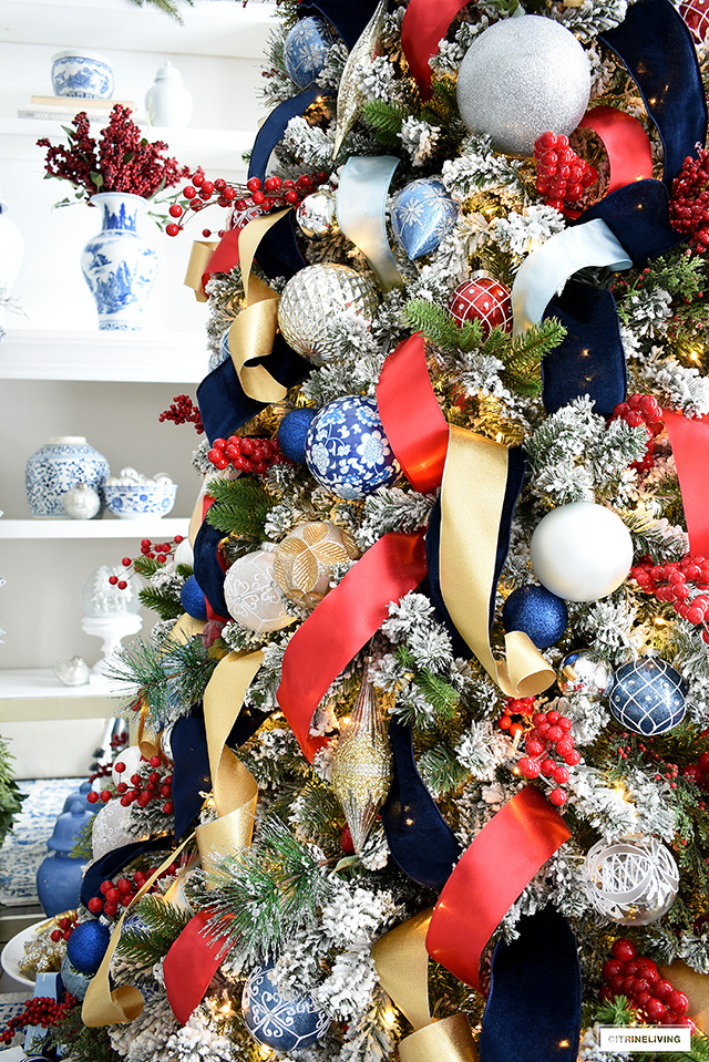 Beautiful flocked Christmas tree with greenery picks, berry picks, and rich colourful decorations.
