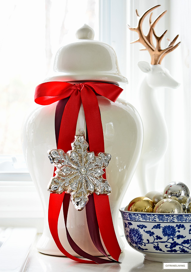 A classic white ginger jar is elevated with beautiful red ribbon and a gorgeous mercury glass snowflake ornament!