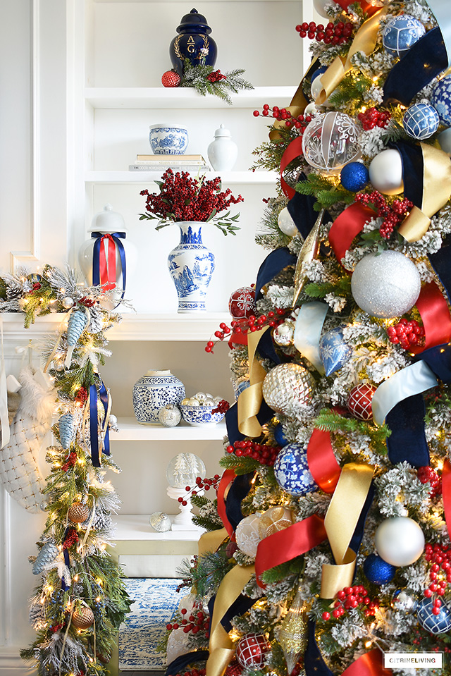 Gorgeous Christmas tree decorated in blue, red, gold and silver - artfully arranged bookshelves with blue and white, ginger jars, ornaments and pine and berry touches.