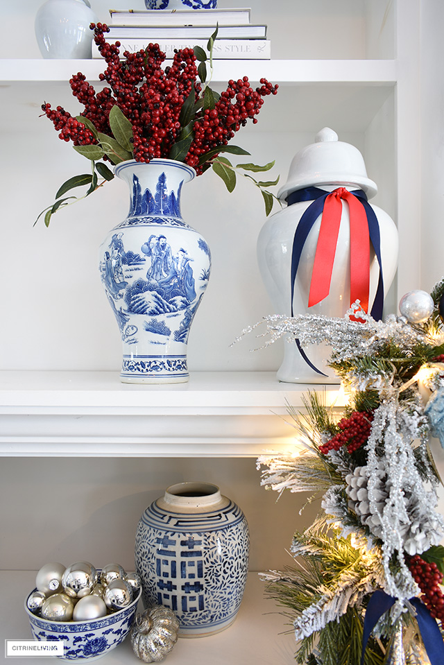 Bookshelf styling for Christmas - ginger jars dressed in ribbon, blue and white vase with red berries.