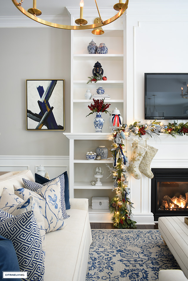 Bookshelves styled for Christmas with a gorgeous garland, blue and white ginger jars and red berries.