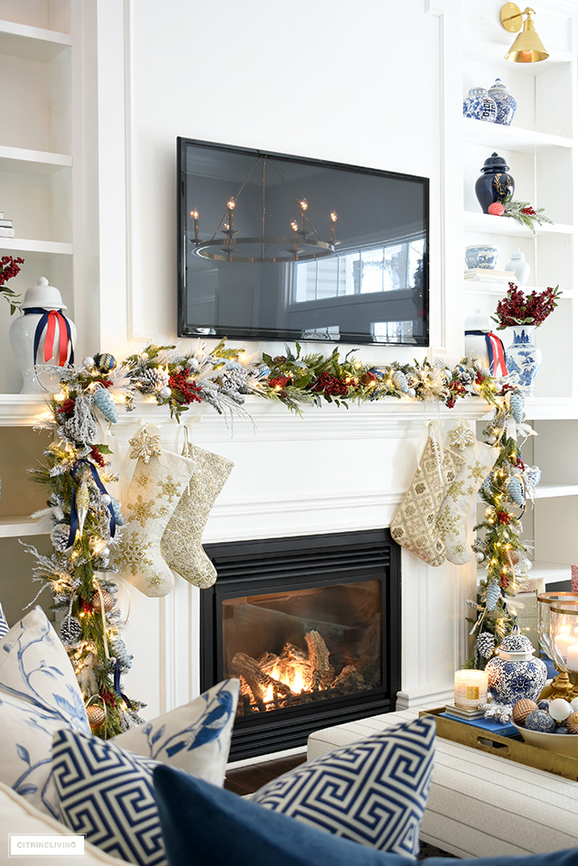 Beautiful Christmas garland decorated with ornaments and ribbon, red berries and lights.