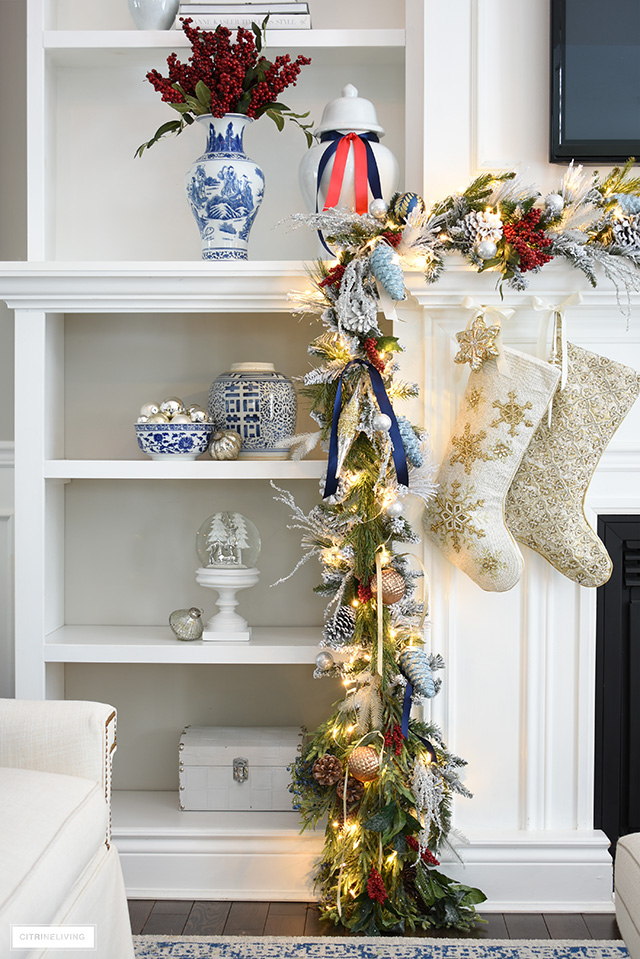 Christmas bookshelves styled with blue and white chinoiserie, beaded stockings and garland.