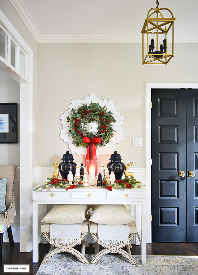 Sophisticated Christmas decorating - console table with ginger jars, holiday greenery, and a gorgeous lush wreath hung above.