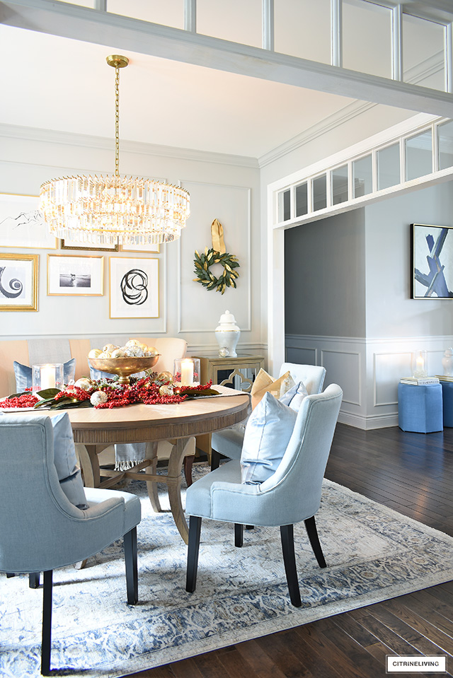 A sophisticated dining room with light blue chairs, round table, vintage style rug and crystal chandelier is decorated for Christmas with simple and elegant decor.