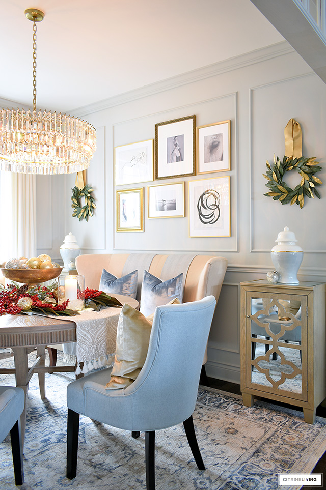 Dining room styled for Christmas with magnolia wreaths hung on the wall and ornaments arranged on the table with a pretty red berry centerpiece.