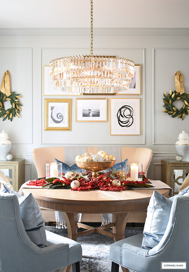 Sophisticated dining room table Christmas centerpiece with red berries and pretty ornaments.