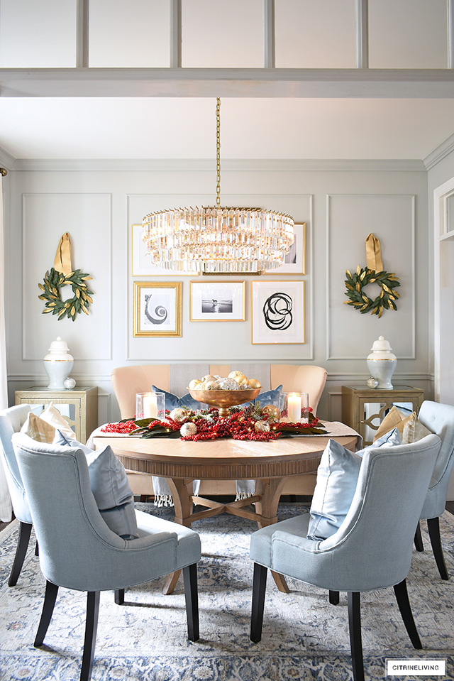 A sophisticated dining room decorated for Christmas with a beautiful red berry centerpiece.