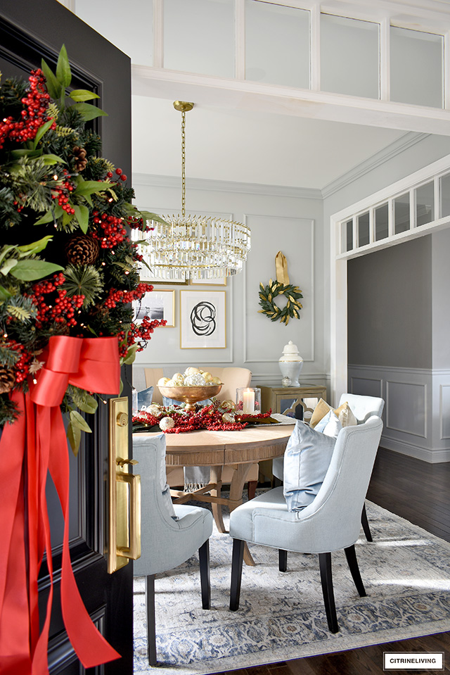 Front door with a beautiful Holiday wreath is open with a view into a beautiful dining room decorated for Christmas.