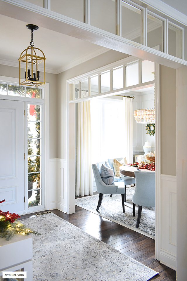 A view into and entryway and dining room space that is open to each other, decorated for Christmas with sophisticated style.
