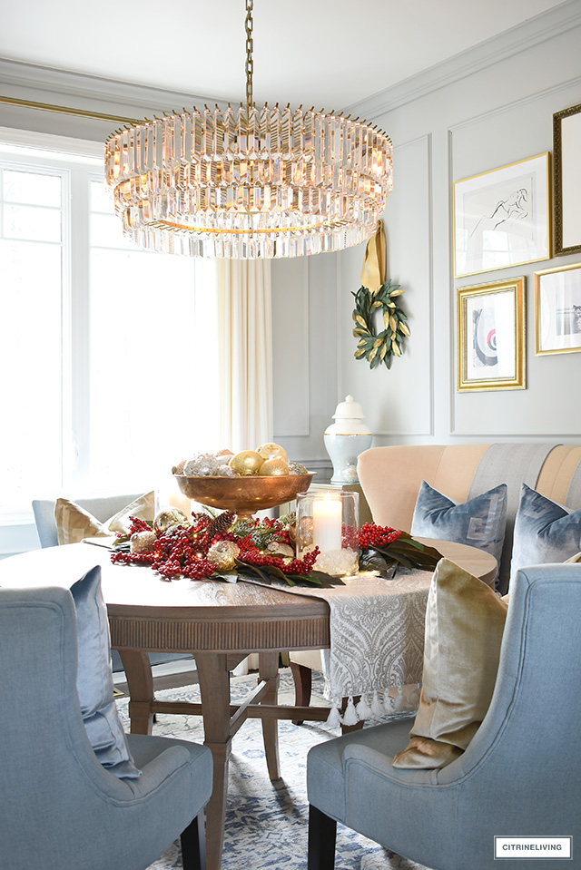 A beautiful Christmas centrepiece on a dining room table, with a gold bowl filled with ornaments surrounded by a red berry and magnolia leaf display.